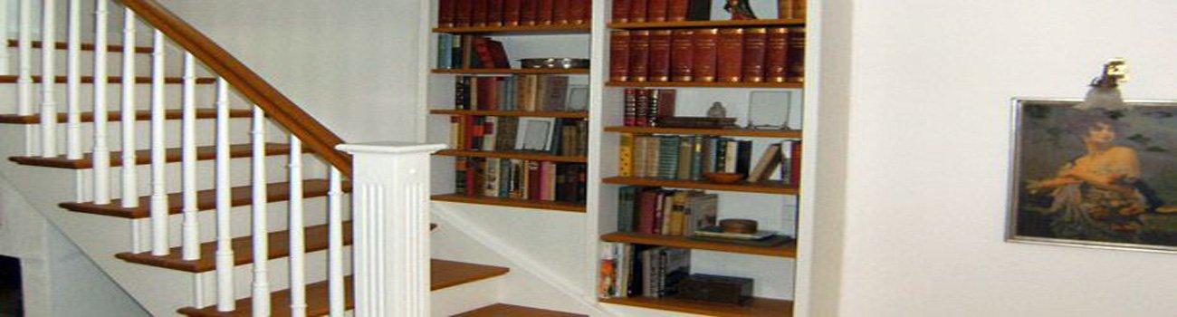 Wendeltreppe mit weißem Geländer und Bücherregal