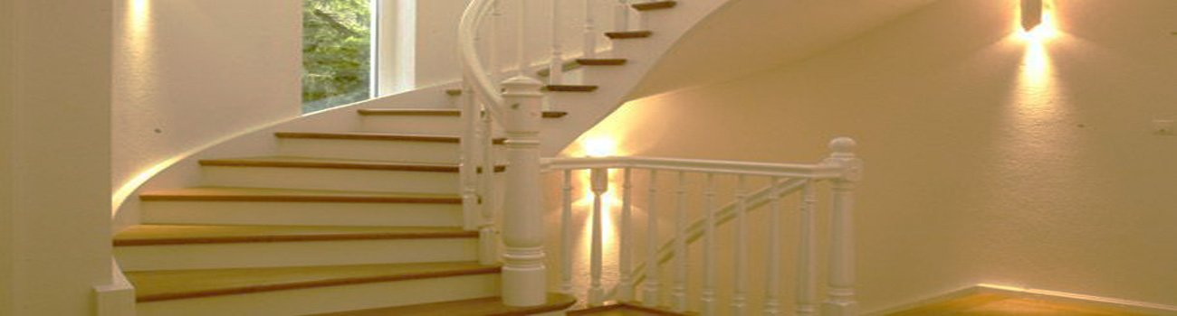 Wendeltreppe mit weißem Geländer aus Holz