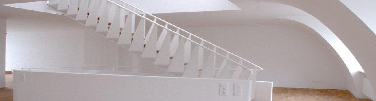Wendeltreppe mit weißem Geländer und weißer Wand